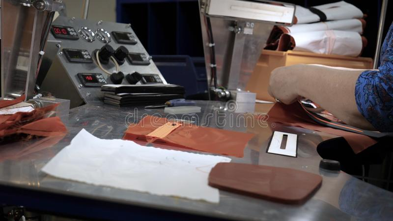 In a slow motion video in a garment factory, women press cut various pieces of clothing and fabric locks and various materials u. Sing different machines stock image