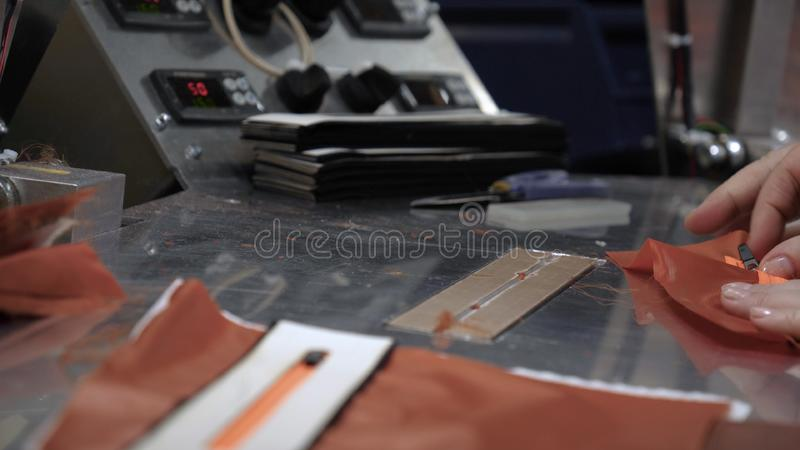 In a slow motion video in a garment factory, women press cut various pieces of clothing and fabric locks and various materials u. Sing different machines stock photography
