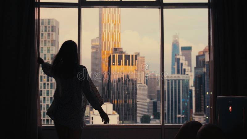 Silhouette of young woman uncover the big window in apartment on the city buildings background. Sunset in the city. royalty free stock images