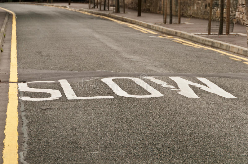 Slow sign on a bend in Edinburgh road, UK. Slow sing on the road written with white color in Edinburgh, UK stock image