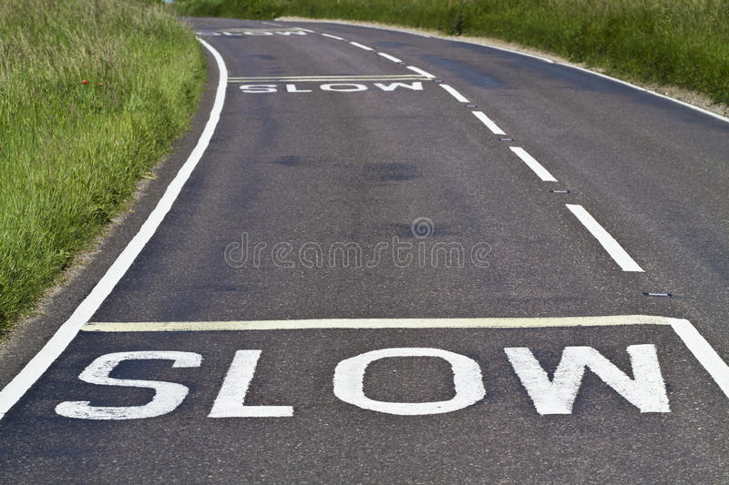 Slow signs on the road. Three warning signs to slow down painted on a curving road royalty free stock image