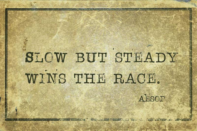Slow but steady Aesop. Slow but steady wins the race - famous ancient Greek story teller Aesop quote printed on grunge vintage cardboard royalty free stock photography