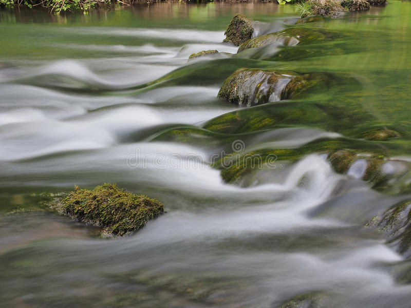 Slow water with moss covered stone royalty free stock photography