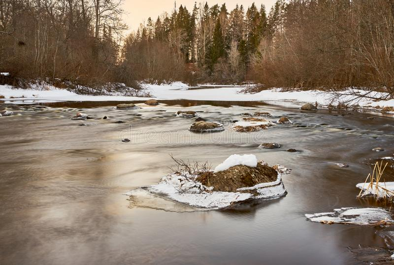 Slowly streaming river. Evening sunny ice  x-default reflecting floided flooded spring clear calm reflection riverbend snow  rocks frosty nature stock images