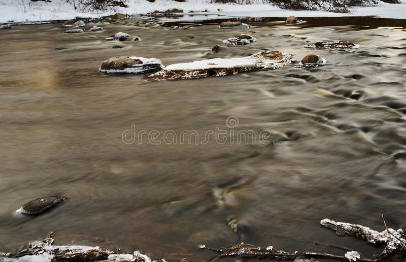 Slowly streaming river. Evening sunny ice  x-default reflecting floided flooded spring clear calm reflection riverbend snow  rocks frosty nature royalty free stock photo