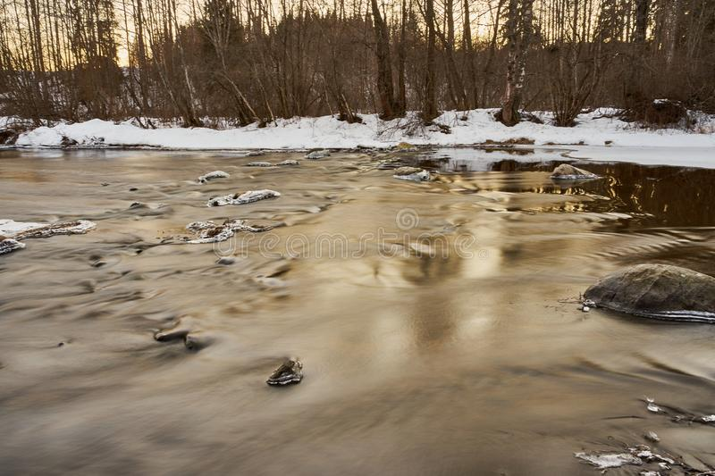 Slowly streaming river. Evening sunny ice  x-default reflecting floided flooded spring clear calm reflection riverbend snow  rocks frosty nature stock photography