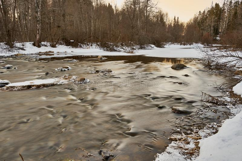 Slowly streaming river. Evening sunny ice  x-default reflecting floided flooded spring clear calm reflection riverbend snow  rocks frosty nature stock photo