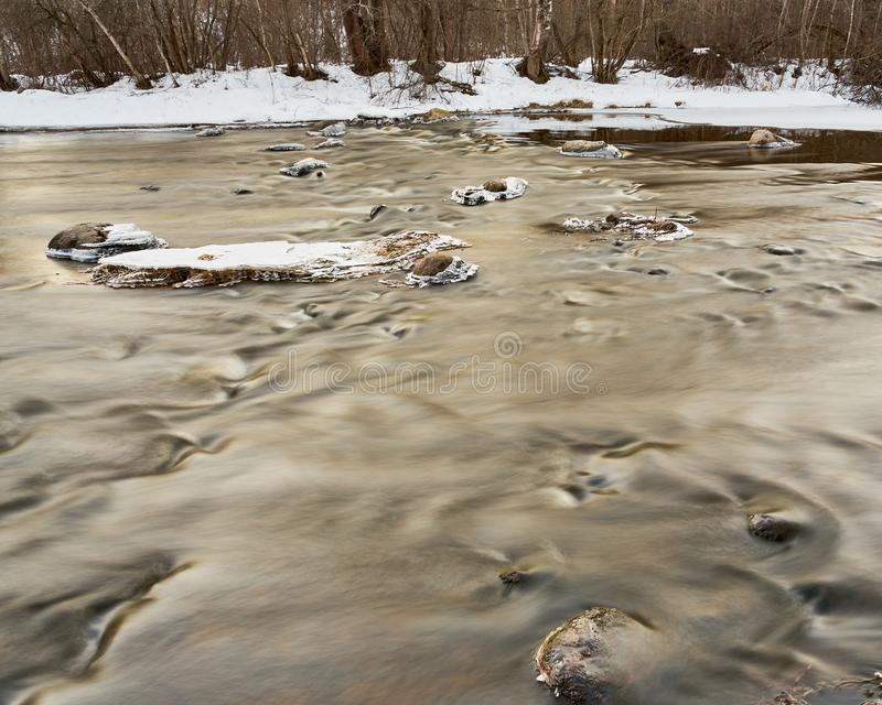 Slowly streaming river. Evening sunny ice  x-default reflecting floided flooded spring clear calm reflection riverbend snow  rocks frosty nature royalty free stock photos