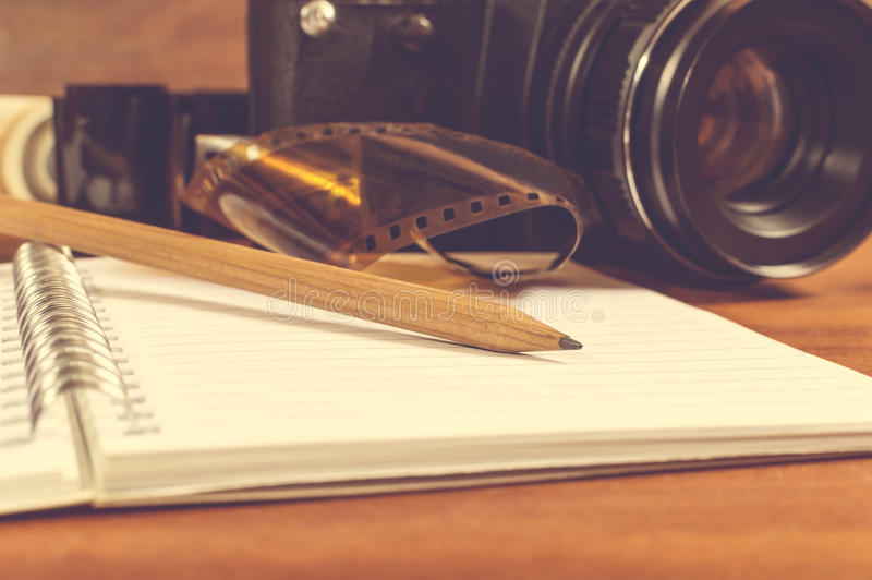SLR camera on the table next to negative film strip and pencil. Old SLR camera on the table next to negative film strip, and in the foreground a notebook and stock images