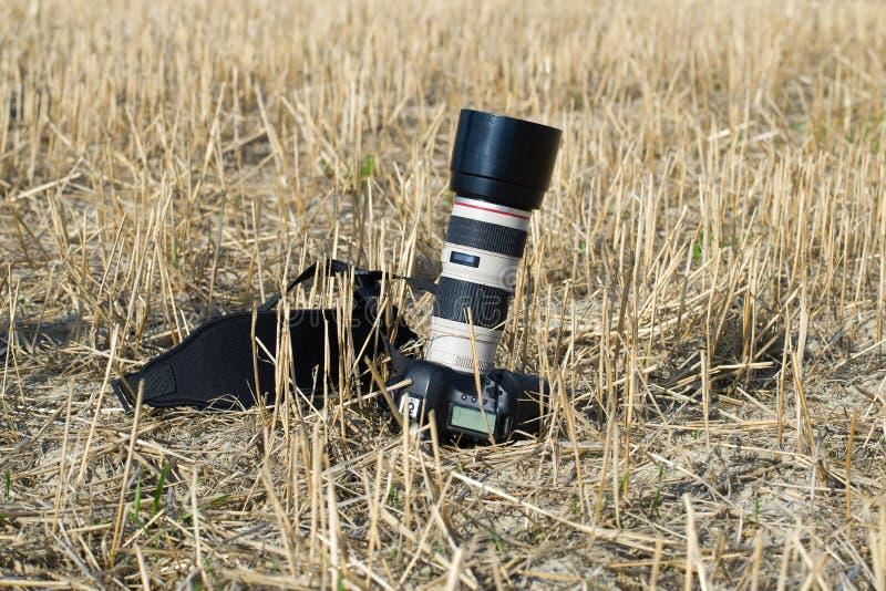 SLR-Kamera mit Teleobjektiv liegt auf einem abgeschrägten Feld stockfotografie