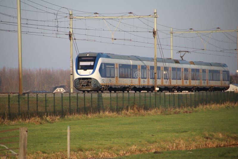 SLT local commuter train at a railroad crossway at nieuwerkerk aan den IJssel in the Netherlands royalty free stock photography