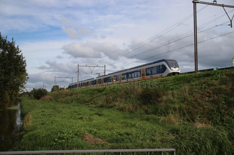 SLT sprinter train in white, blue and yellow as local commuter at railroad track in Nieuwerkerk aan den IJssel in the Netherlands. stock photos