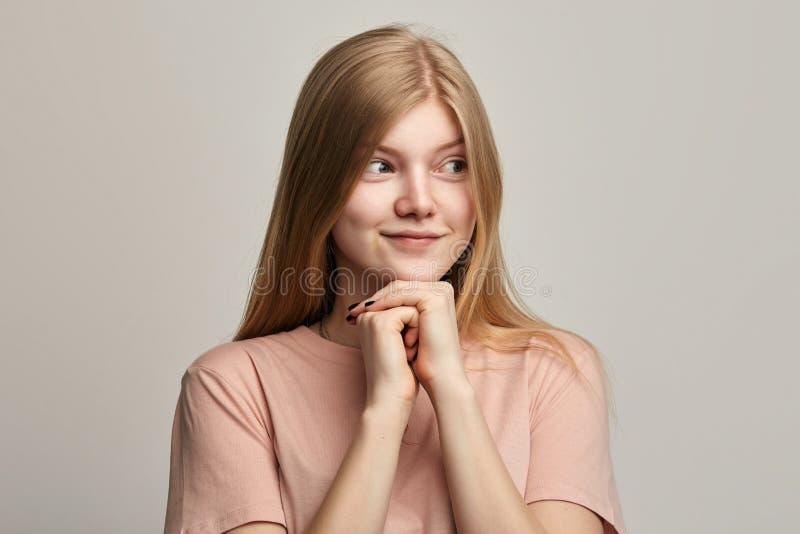 Slug härlig flicka som planerar det onda tricket som framme rymmer händer av hennes bröstkorg royaltyfri foto