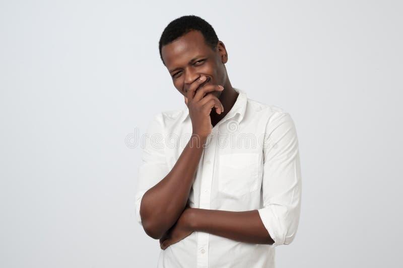 Slug listig afrikansk man som trycker på hakan med fingret och bort ser Stiligt tänka för grabb fotografering för bildbyråer