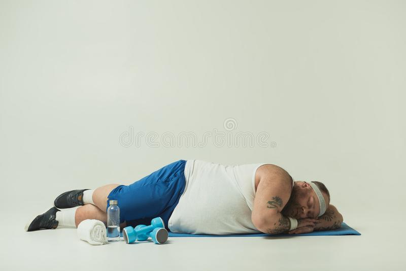 Lazy thick guy slumbering after workout. Sluggish fat man is sleeping on sport mat instead of training. Dumbbells and bottle of water on floor stock image
