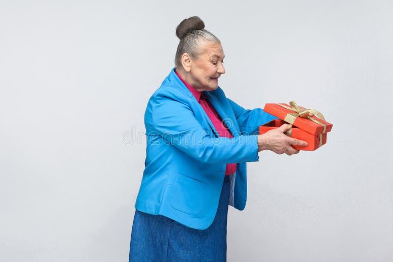 Slugheten åldrades kvinnablick inom gåvaasken royaltyfri foto