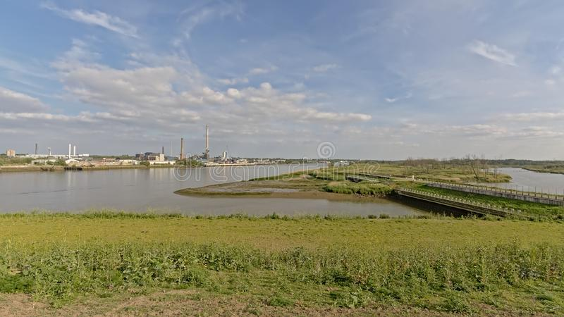 Sluice on a side-arm of river Scheldt in Antwerp with industrial buildings of the harbor in the background. Sluice on a tributary of river Scheldt in Antwerp royalty free stock photo