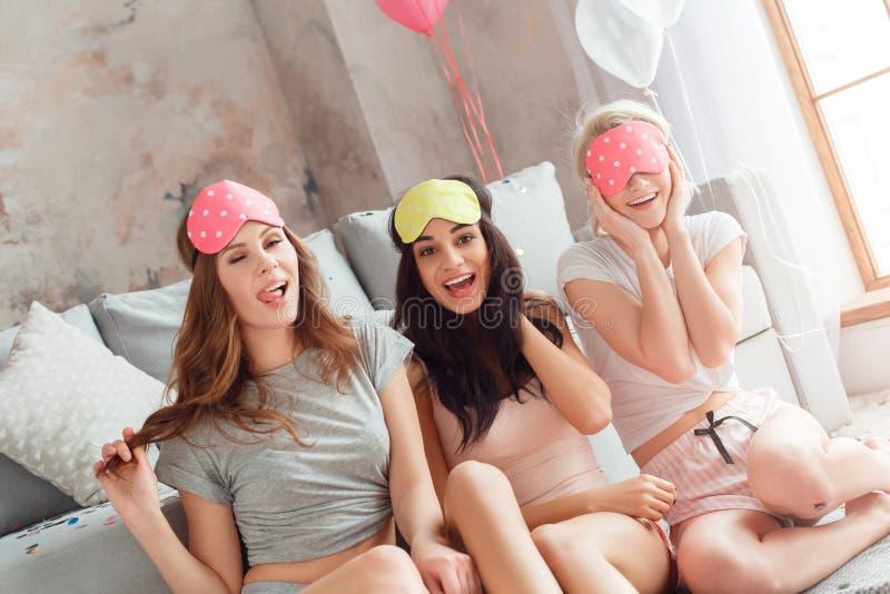 Sluimerpartij De jonge vrouwen in slaap maskeren samen thuis het zitten op vloer glimlachend speels close-up stock fotografie