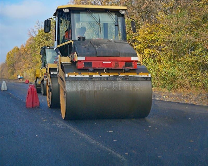 Sluit asfalt het bedekken omhoog machine die op nieuwe weg rollen stock foto's