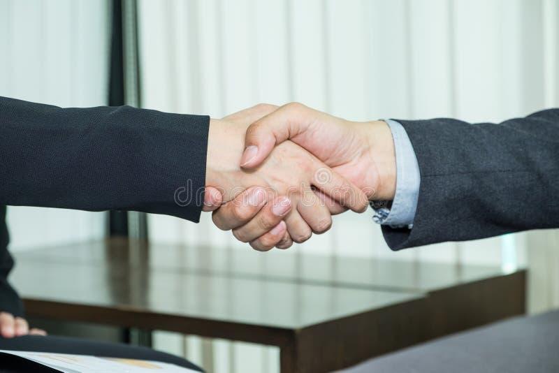 Sluit Aziatische bedrijfsmensenhanddruk behandelen omhoog overeenkomst bij stock foto's