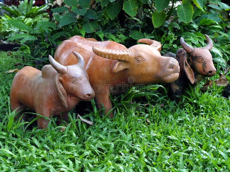 Sluit buffels en koe gebakken kleipop die zich op groen grasgebied omhoog bevinden in het midden van versheids weelderige struik stock fotografie