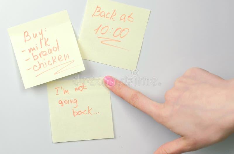 Sluit de documenten van de de stokken omhoog gele sticker van de vrouwen` s hand nota's over een witte raad Familienota's royalty-vrije stock fotografie