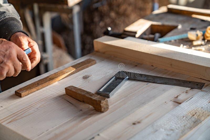 Sluit de foto, handmatige verwerking van hout in de thuiswerkplaats van de timmerman, de meester werkt met een vredelievende krac royalty-vrije stock fotografie