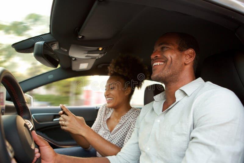 Sluit de omhoog glimlachende Afrikaanse Amerikaanse mens en vrouw in auto het glimlachen royalty-vrije stock foto
