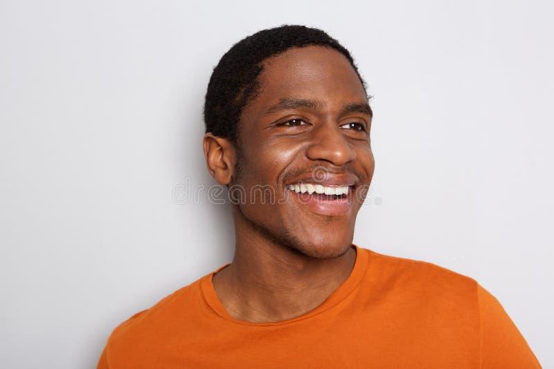 Sluit de omhoog glimlachende Afrikaanse Amerikaanse mens tegen witte muur stock foto