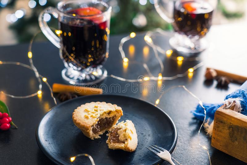 Sluit gebroken Mince Pie af met opvulling op zwarte plaat, gemulgeerde wijndranken en licht land op donkere tafel achtergrond Tra stock afbeeldingen