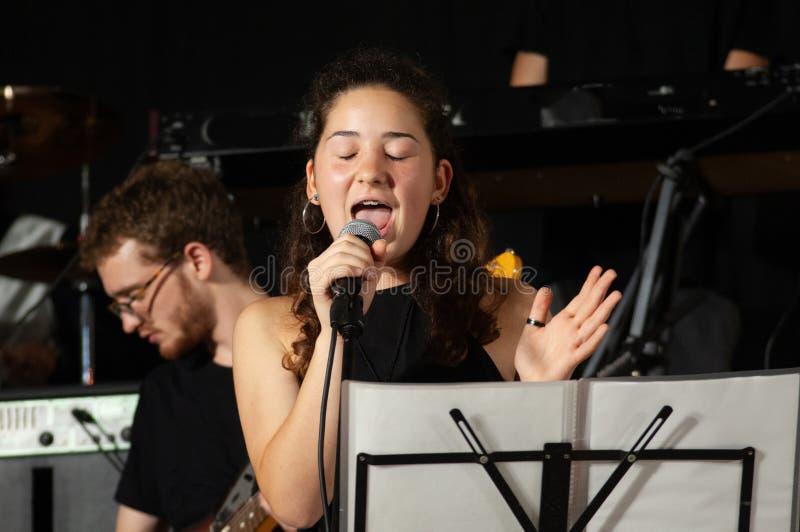 Sluit gezichts omhoog mooi jong brunette, vocalistzanger met microfoon, terwijl zingen levend, met jonge gitarist op achtergrond stock afbeeldingen