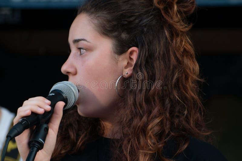 Sluit gezichts omhoog mooi jong donkerbruin meisje, vocalistzanger met microfoon, terwijl zingen levend, met zwarte kleding stock foto