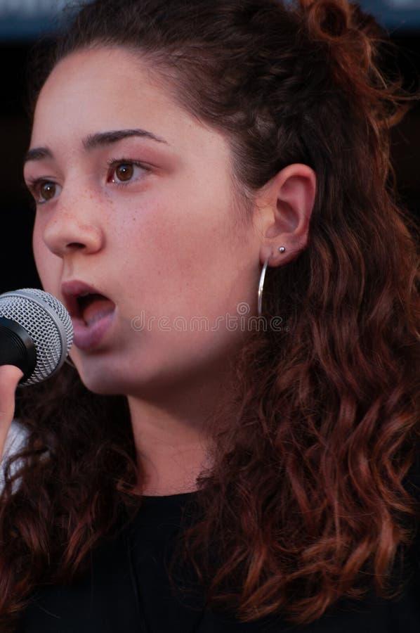 Sluit gezichts omhoog mooi jong donkerbruin meisje, vocalistzanger met microfoon, terwijl zingen levend, met zwarte kleding stock foto's