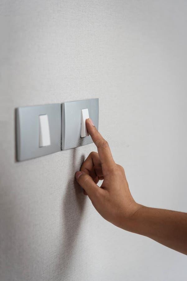 Sluit hand omhoog het aanzetten of weg op grijze lichte schakelaars stock foto