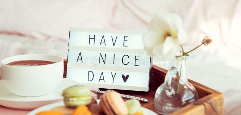 Sluit hebben omhoog een aardige dagtekst op aangestoken vakje op het dienblad met ontbijt in bed Kop van koffie, makarons, bloem  stock foto