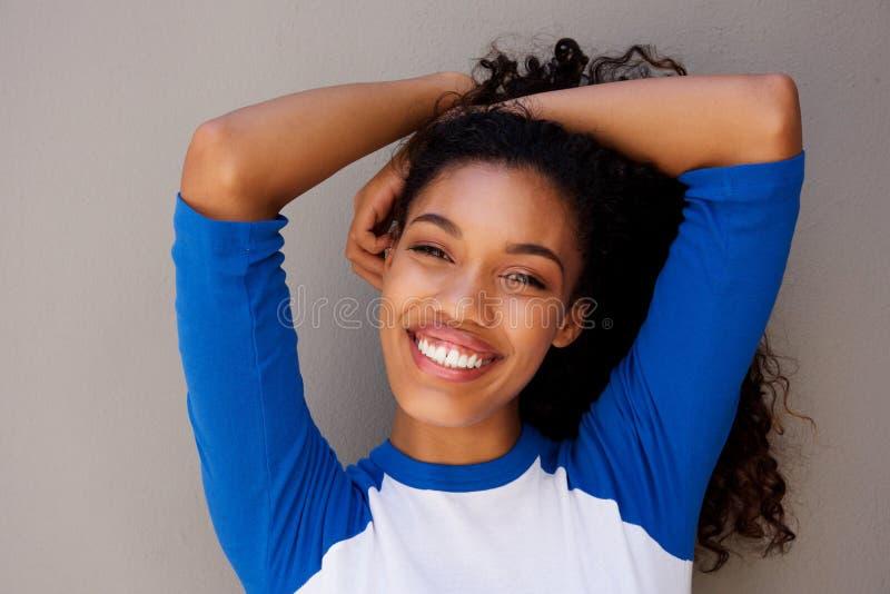 Sluit het mooie jonge Afrikaanse Amerikaanse vrouw glimlachen met indienen omhoog haar stock foto's