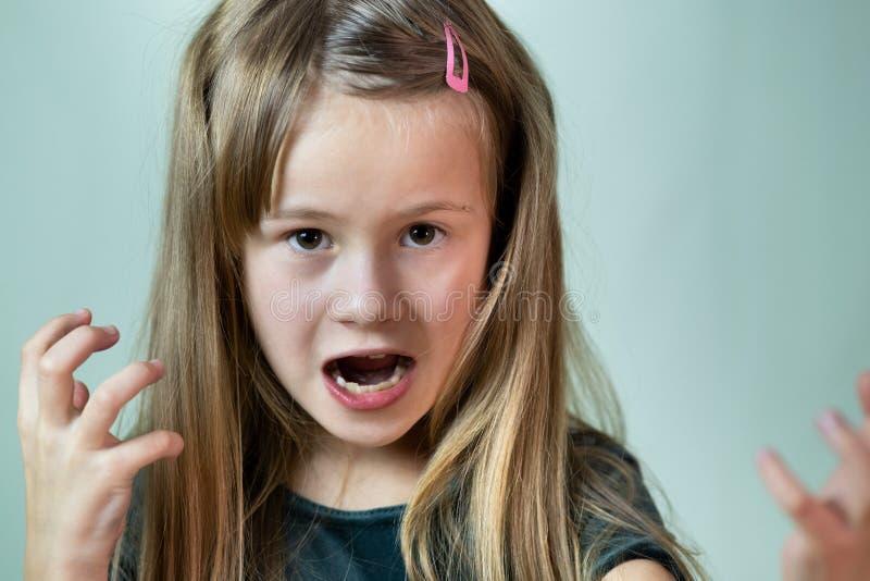 Sluit het portret van boos schreeuwend kindmeisje dat er agressief uitziet in camera stock foto's