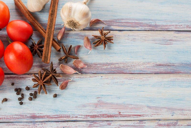Sluit knoflook, rode tomaat, omhoog kruiden en kruiden op een houten lijstbedelaars royalty-vrije stock foto's