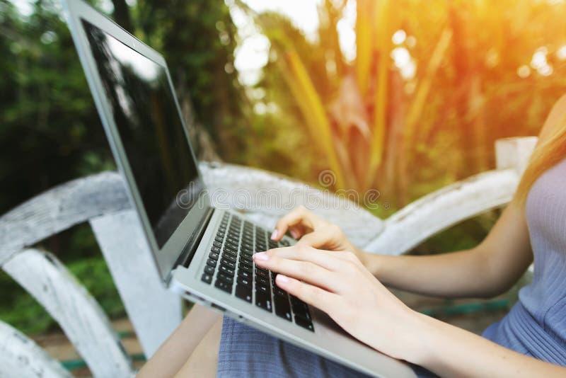 Sluit laptop van de de vingerspers van de vrouwenhand omhoog toetsenbord voor het verre werk op zonnige dag, achtergrond van zonn royalty-vrije stock afbeelding