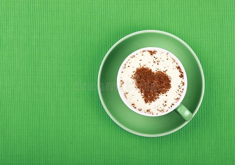 Sluit latte omhoog cappuccinokoffie in kop op groen stock foto