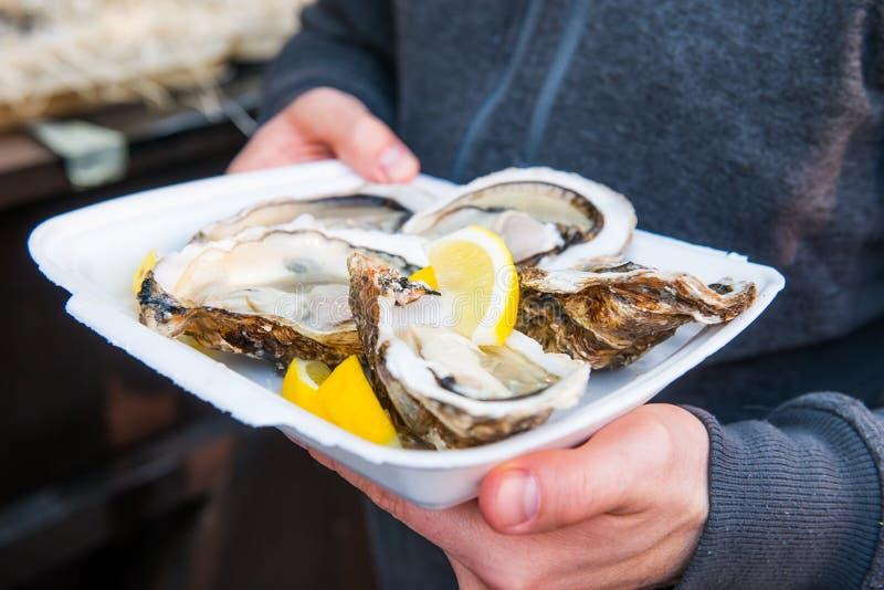 Sluit mannelijke handholding weghalen omhoog voedseldienblad met verse geopende oester en citroenplakken bij de markt van het str royalty-vrije stock afbeelding