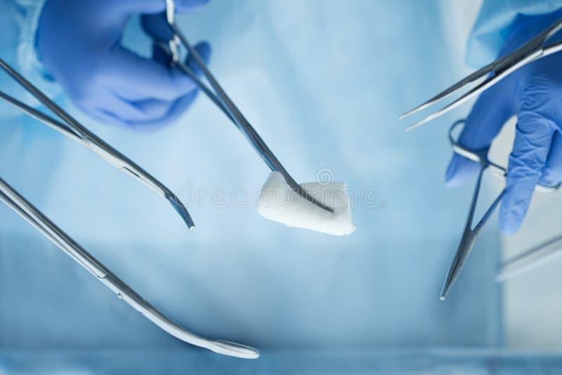 Sluit mening die van artsenhanden chirurgische hulpmiddelen omhoog houden stock foto