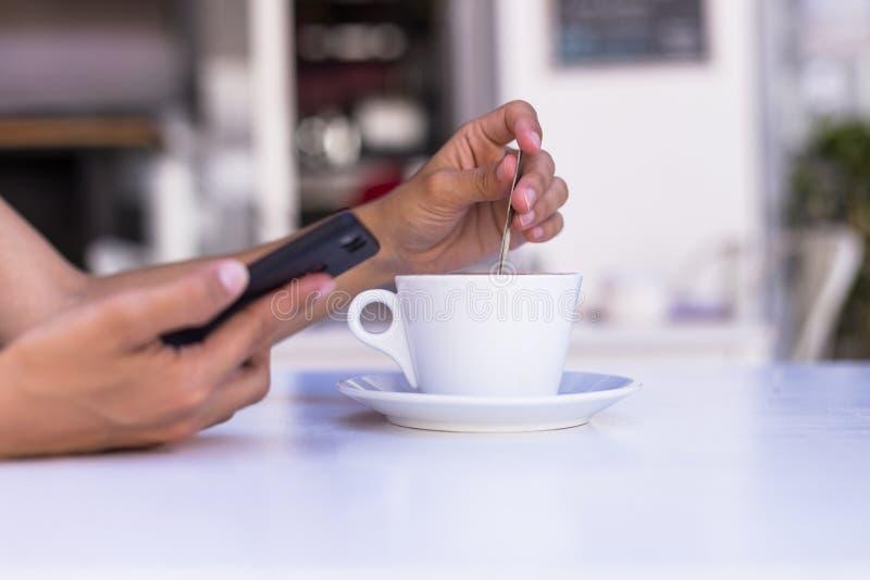 sluit mening die van vrouwenhanden een kop van koffie en mobiele telefoon in een terras omhoog houden Ochtend, dag en technologie stock fotografie