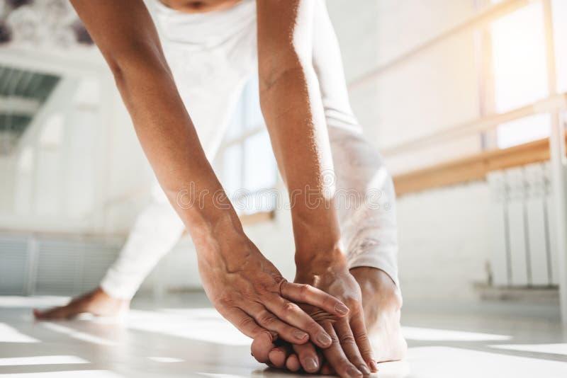 Sluit mening over jongelui taned omhoog geschikte vrouw die het uitrekken zich oefeningenbeen in witte binnenlandse gymnastiek do stock foto's