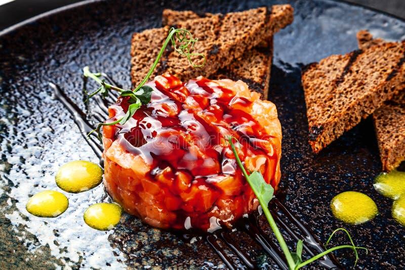 Sluit mening over zalm tartare met brood, saus en peterselie op zwarte ceramische plaat omhoog wordt gediend die De vlakte van Ta stock afbeelding