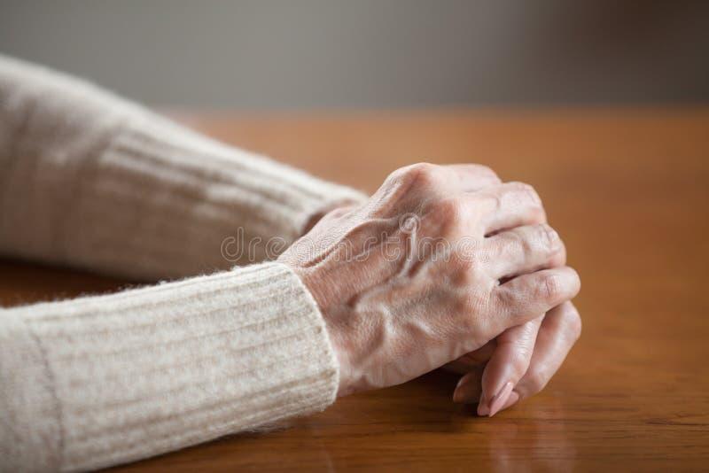 Sluit mening van rijp wijfje rimpelde omhoog handen op lijst stock fotografie