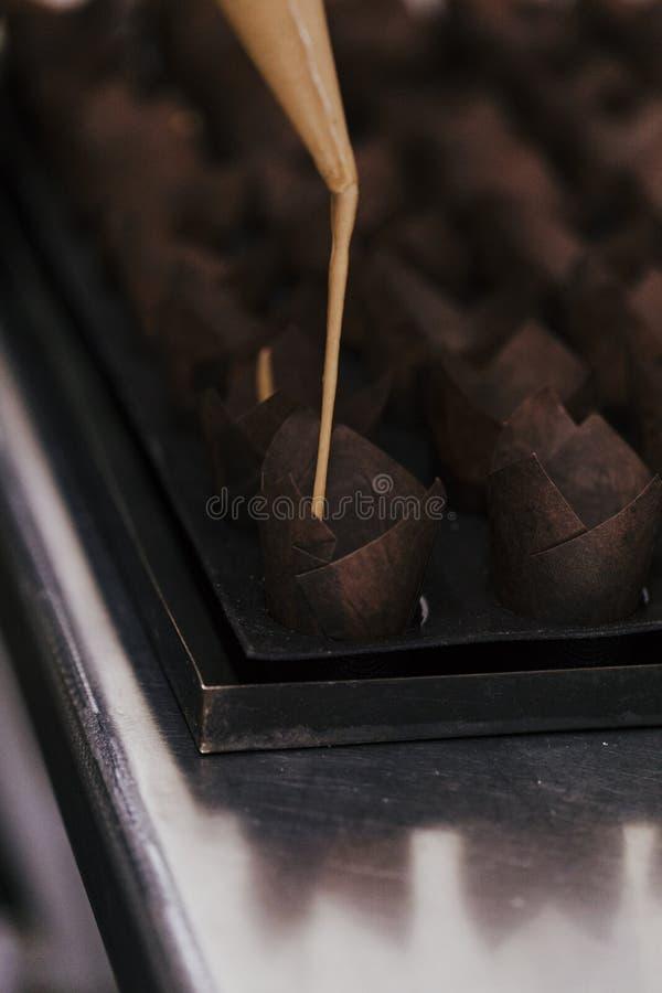 Sluit mening van vrouw indienen omhoog gebakjebakkerij als banketbakker die muffins met suikerglazuurzak voorbereiden stock afbeeldingen