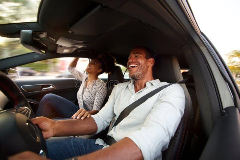 Sluit mens en vrouw die en samen in auto glimlachen omhoog de zitten stock foto's