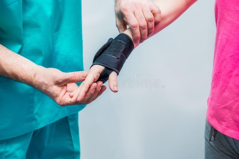 Sluit Neuroloog omhoog arts, zet de therapeut op polspal op de jonge vrouwelijke geduldige hand van ` s Pijnbehandeling Neurologi stock afbeeldingen