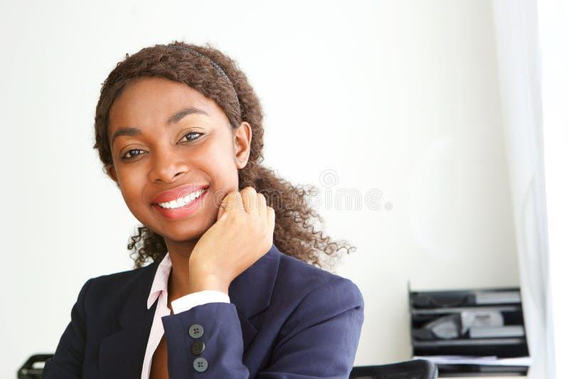 Sluit omhoog aantrekkelijke jonge Afrikaanse onderneemster die in bureau glimlachen royalty-vrije stock fotografie